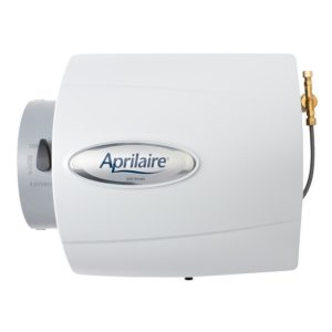 The Aprilaire 500 humidifier faces the camera and has a tube coming out from the side of the appliance