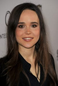 A smiling Ellen Page looks to the camera at a red carpet event wearing her hair long, straight, and down