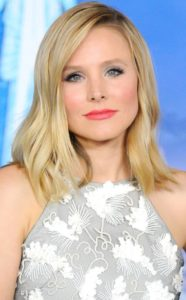 Kristen Bell smiles faintly as she looks to the camera