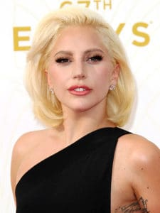 Lady Gaga smirks to the camera wearing a one-shoulder black dress