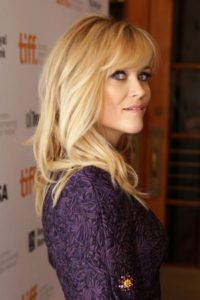 The actress looks seductively to the side, towards the camera, from under her blond fringe