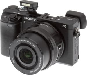 The Sony a6300 camera is placed at an angle with the shutter open and flash mechanism out of the main body