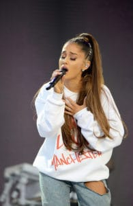 The singer performs at the Manchester One Love concert, resting her right hand on her chest, with her eyes closed