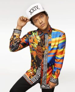 Bruno Mars poses for a photograph, holding with one hand his white cap in place and wearing a colorful shirt