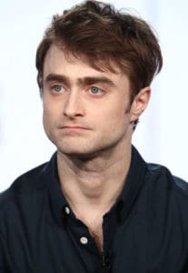 Daniel Radcliffe looks to the side of the camera with a serious look on his face