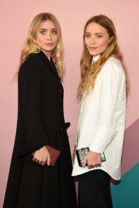 The twins stand facing each other and looking in the camera, wearing contrasting white and black clothes