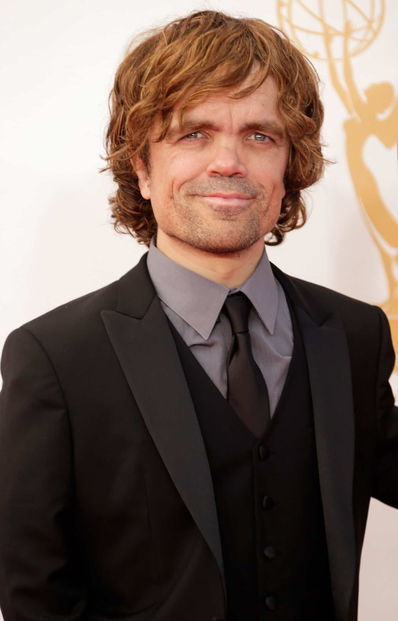 Peter Dinklage smiles to the camera at a red carpet Hollywood event, dressed in a suit and tie