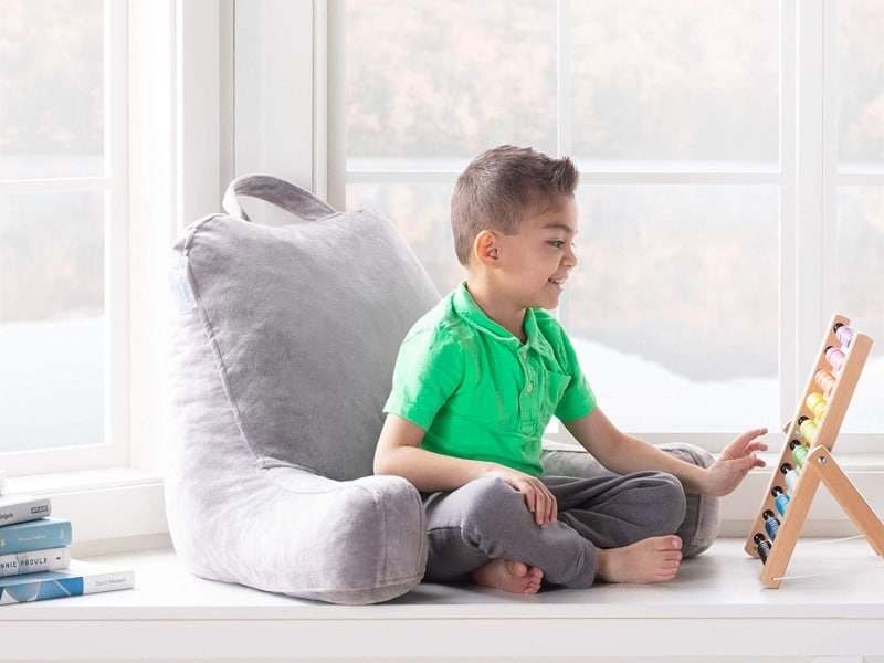 Child resting on husband pillow and doing math