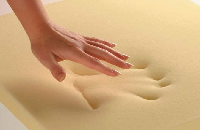 A woman presses down on memory foam and leaves a hand print