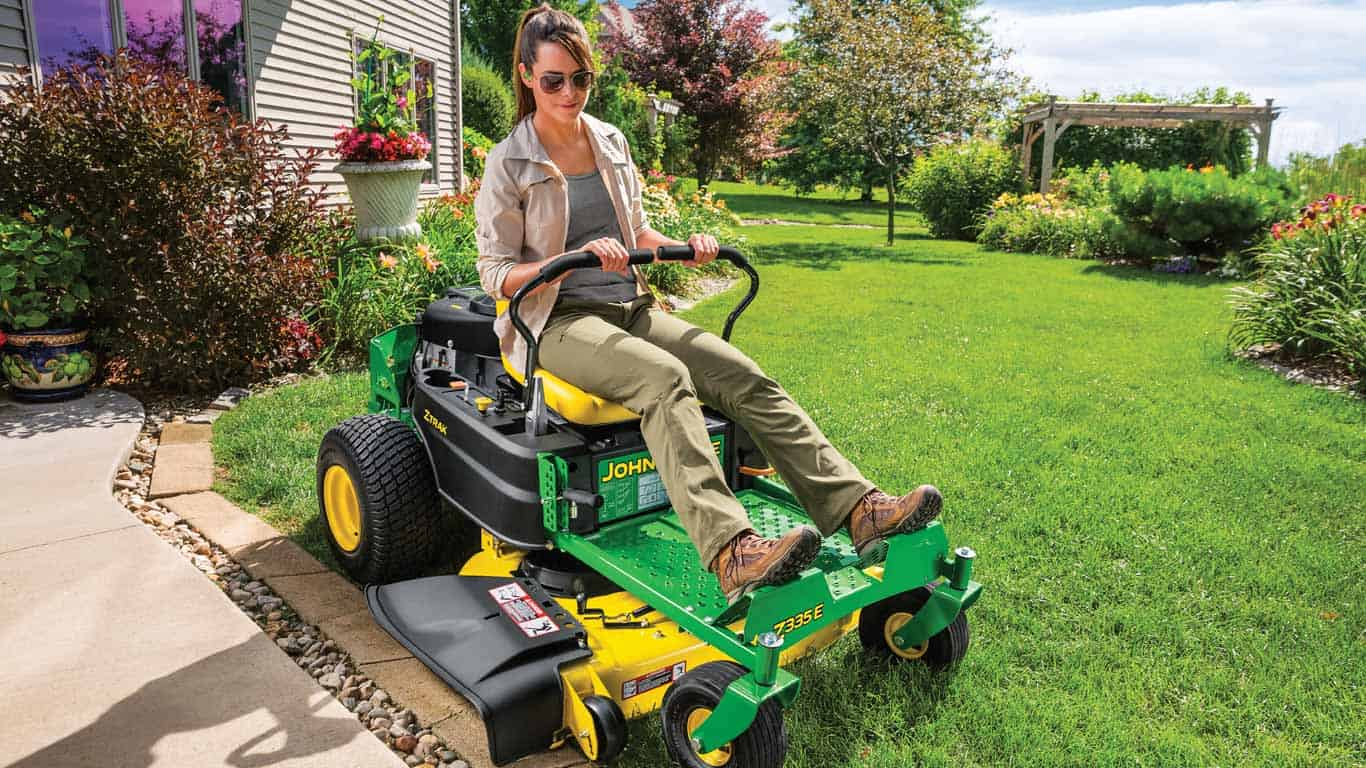 A woman rides a zero turn mower
